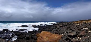 Orange und schwarze Felsen auf Ozeanufer lizenzfreies stockfoto