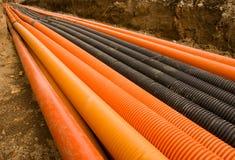 Orange und schwarze Plastikrohre Stockbild