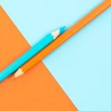 Orange und Türkis farbige Bleistifte und Papier Lizenzfreie Stockfotos