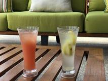 Orange und transparentes Cocktail auf hölzernem Couchtisch Lizenzfreie Stockfotos