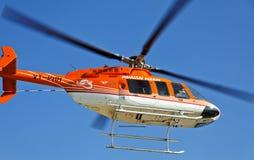 Orange und weißer Hubschrauber obenliegend stockfoto