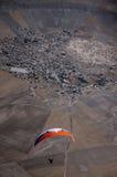Orange und weißes Gleitschirmpilotfliegen über dem Dorf durin Stockbild
