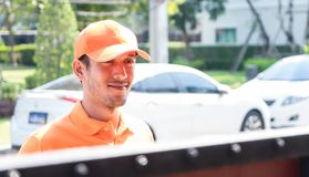 Orange uniform Delivery man waiting at the gate royalty free stock photo