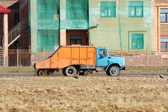 Orange urban sweeper cleans road from dirt with a round brush in the spring. Royalty Free Stock Photos