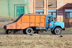 Orange urban sweeper cleans road from dirt with a round brush in the spring. Stock Images
