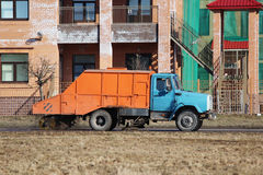 Orange urban sweeper cleans road from dirt with a round brush in the spring. Royalty Free Stock Photography
