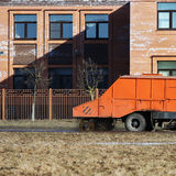 Orange urban sweeper cleans road from dirt with a round brush in the spring. Royalty Free Stock Photo