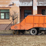 Orange urban sweeper cleans road from dirt with a round brush in the spring. Royalty Free Stock Images