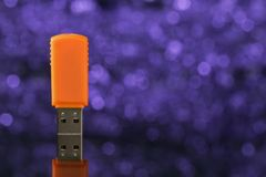 Orange USB-Blitz-Antrieb auf violettem Hintergrund unscharf Lizenzfreie Stockfotos
