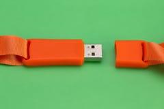 Orange USB-Flash-Speicher auf einem grünen Hintergrund Stockfotografie