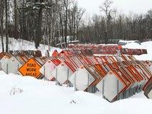 Orange VÄGARBETE FRAMÅT att underteckna bland dussintals vägmärken i en snöig lott royaltyfria bilder