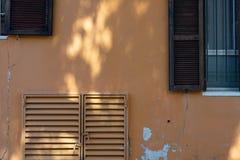Orange vägg för abstrakt bakgrund med skivor av fönster med träbruntslutare och metallskyddsgallrar, solfläckar på murbruk Arkivfoton