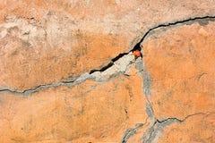 Orange vägg med en spricka arkivfoto