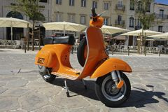 Orange Vespa. Parked on the sidewalk Royalty Free Stock Photos