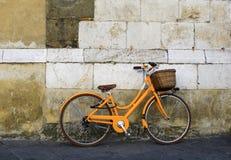 Orange vintage bicycle near old wall stock photos