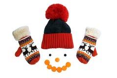 Orange vinterhatt med tamburin och varma tumvanten med smileycirklar av skivade morötter på en vit Fotografering för Bildbyråer