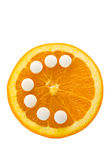 Orange with vitamin c pills. Orange half with vitamin c tablets spelling the letter c on an isolated background including a clipping path Stock Image