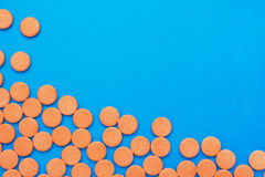 Orange vitamin pills. On a blue background Royalty Free Stock Image