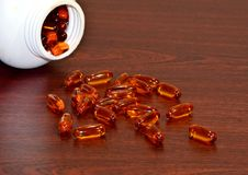 Orange vitamins in capsules lie on the table stock photography