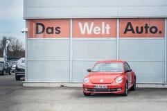 Orange Volkswagen nytt utskjutande framme av den Volkswagen visningslokalen Arkivfoton