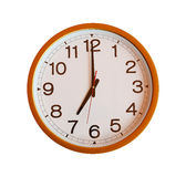 Orange wall clock isolated in seven o'clock. Orange wall clock isolated in seven o'clock on white background royalty free stock photography