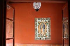 Orange Wall and Saint at Casa Alvarado, Coyoacan, Mexico City. Interior hallway with glass doors showing praying saint traditional religious art stock photo