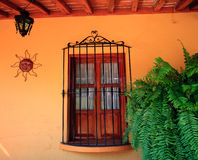 Orange wall with wooden window. Old fashioned stucco wall with window, grille, sun design and lamp royalty free stock photos
