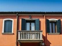 Orange Wand des Hauses mit einem Fenster mit blauen Fensterläden und einem Balkon Stockfotos