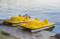 Orange water bicycles anchored at shore Stock Photos