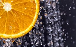 Orange among water droplets royalty free stock photo