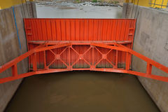 Orange water gate at dam. Royalty Free Stock Images