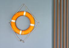 Water sport safety equipment. Orange water safety ring hanging on a gray concrete wall and wooden battens royalty free stock photography