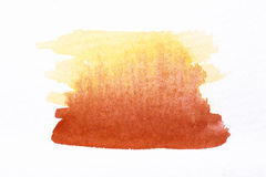 Orange watercolor brush strokes on white rough texture paper Royalty Free Stock Photo