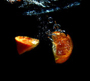 Orange in waterfall. Orange falling in the water Stock Image