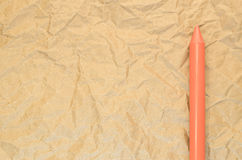 Orange wax crayon on a recycled crumpled paper surface Stock Photo