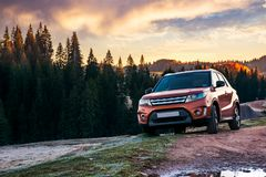 Orange 4wd suv parked in mountain at sunrise. Beautiful autumn scenery with gravel road through spruce forest. travel Europe by car concept royalty free stock images