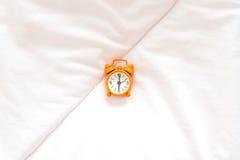 Orange Wecker stehen sechs o'clock auf Bett am Morgen mit Sonnenlicht auf Stockfotos