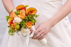 Orange wedding bouquet. Very colorful orange wedding bouquet closeup with bride holding it Royalty Free Stock Photo