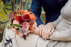 Orange wedding bouquet in hands stock photography