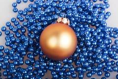 Orange Weihnachtsball und blaue Perlen Stockfotos
