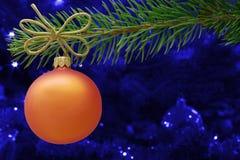 Orange Weihnachtsflitter und ein Fichtenzweig Stockfotos