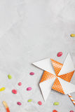 Orange whirligig with white stars and candies on concrete backgr Royalty Free Stock Images
