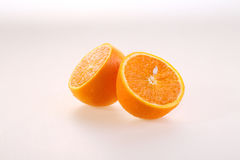 Orange on a white background, halves of a juicy ripe orange on a. White background royalty free stock photo