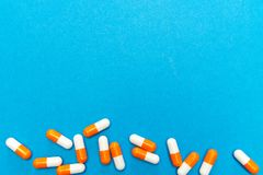 Orange white  capsules pills on a blue background. Medical background, template. Orange white  capsules pills on a blue background. Medical background, template Stock Image