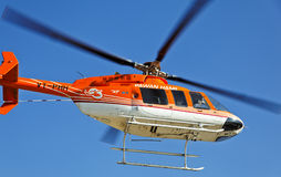Orange and white helicopter overhead Stock Photo