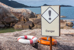 Orange and white life buoys on the rock with danger sign caution Royalty Free Stock Photo