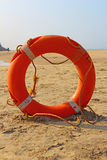 Orange white lifebuoy on the sand Royalty Free Stock Images