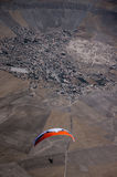 Orange and white paraglider pilot flying above the village durin Stock Image