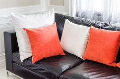Orange and white pillows on modern black sofa in Royalty Free Stock Image