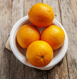 Orange in white plate on wooden background Stock Image